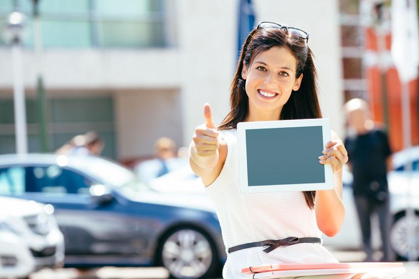 Mujer levantando el pulgar con tablet en mano