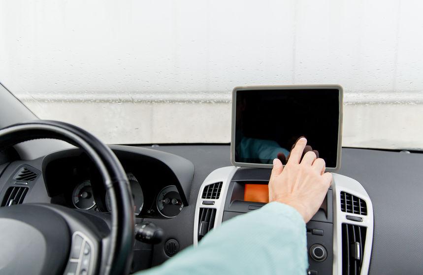Imagen de una ersona tocando tablet en tablero de auto
