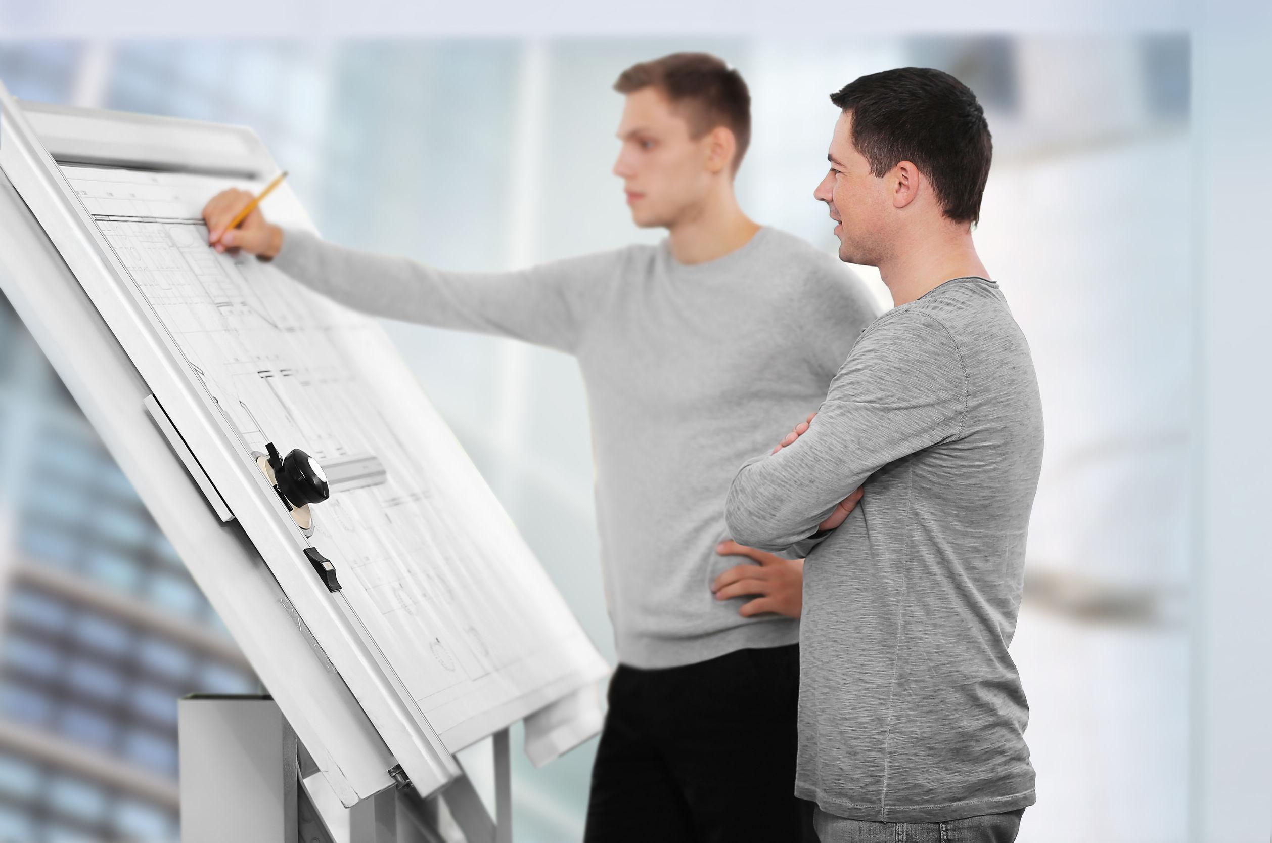 Imagen de dos personas revisando planos en mesa de dibujo