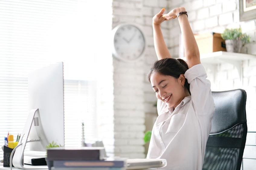 Mujer estirándose en oficina