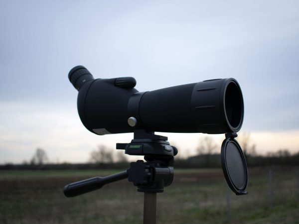 Stargazing or hunting or bird watching spotting scope on a tripod in nature.