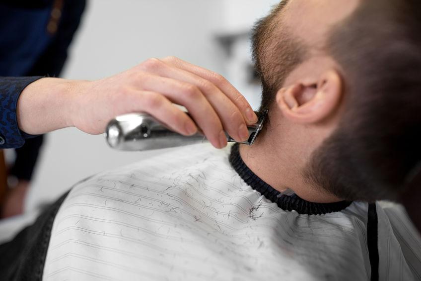 Hombre en peluquería afeitándose la barba