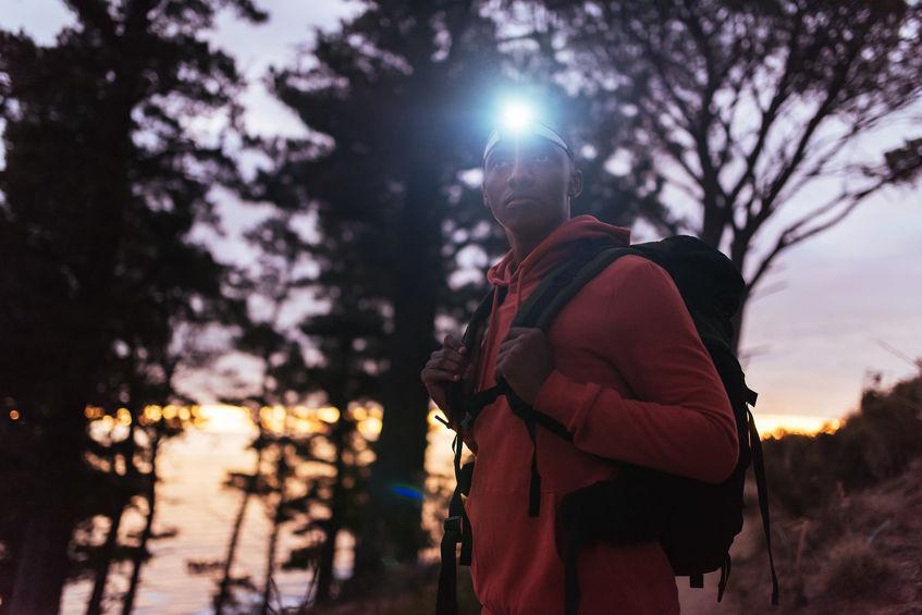 Hombre en bosque con lampara de cabeza