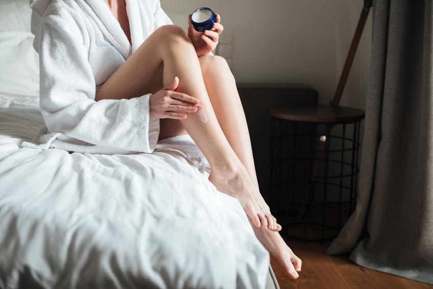 Mujer aplicándose crema cicatrizante en la pierna