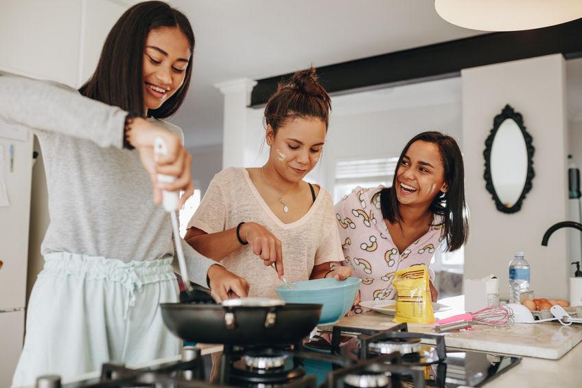 Tres jóvenes cocinando en parrilla de gas