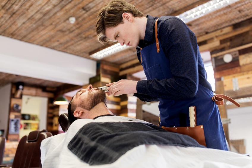 Hombre n peluquería afeitándose la barba