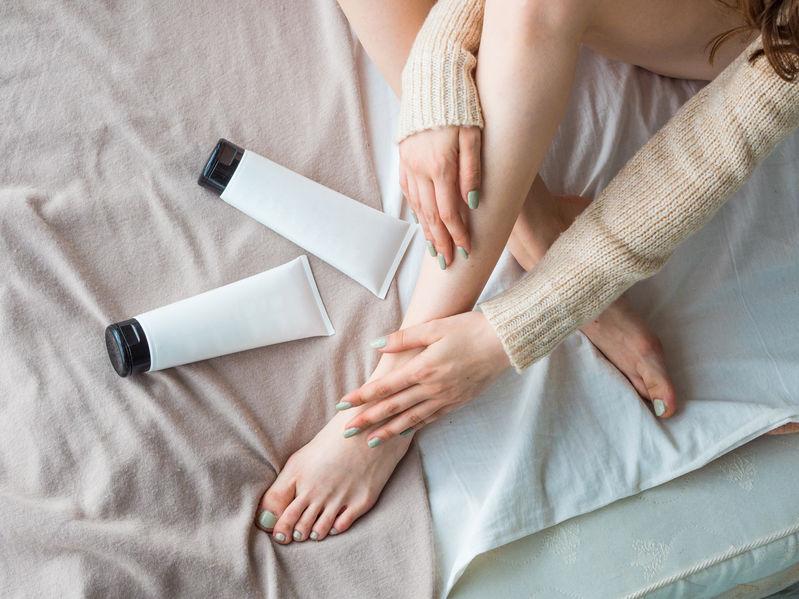 Mujer en cama con cremas cicatrizantes