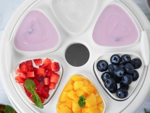 Modern yogurt maker and ingredients on wooden table, closeup