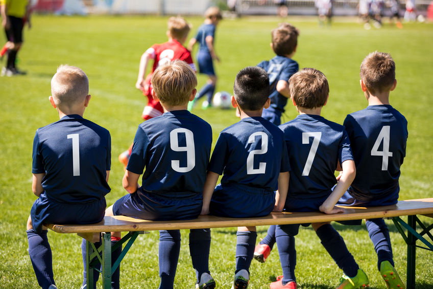 Kids sport team sitting on a bench. Group of kids soccer players. Children football club. Football soccer tournament game for children. Boys kicking soccer ball on grassy pitch. Children play sports outdoors.