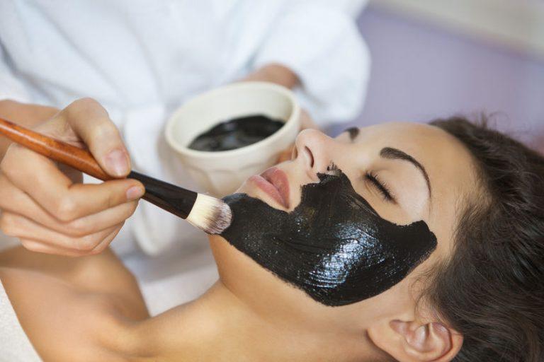 Mujer en spa alicandole mascarilla negra