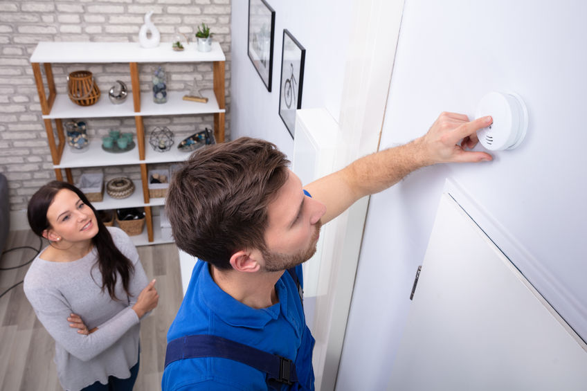 Repairman Installing Smoke Detector On Wall