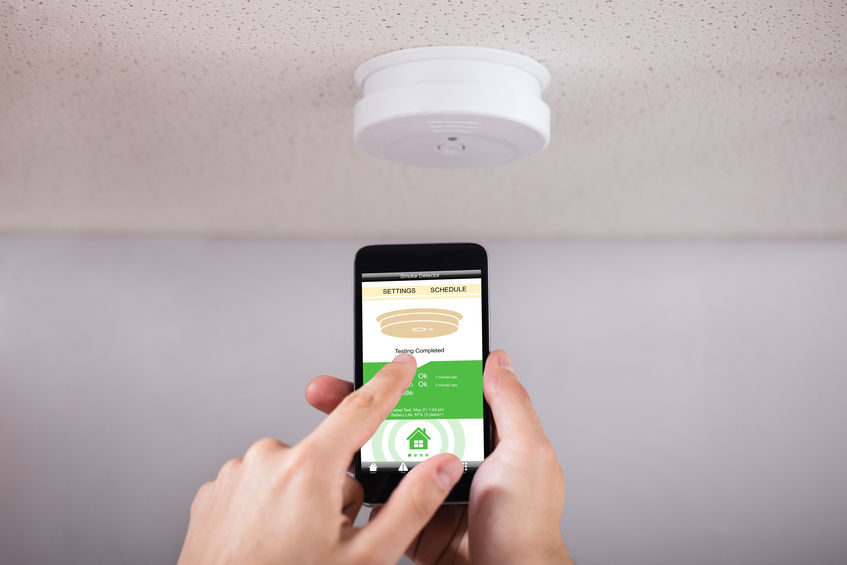 Person Operating Smoke Detector With Mobile Phone