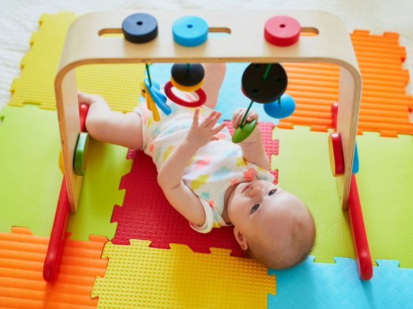 Adorable baby girl having fun with toys on colorful play mat. Happy healthy kid playing on the floor