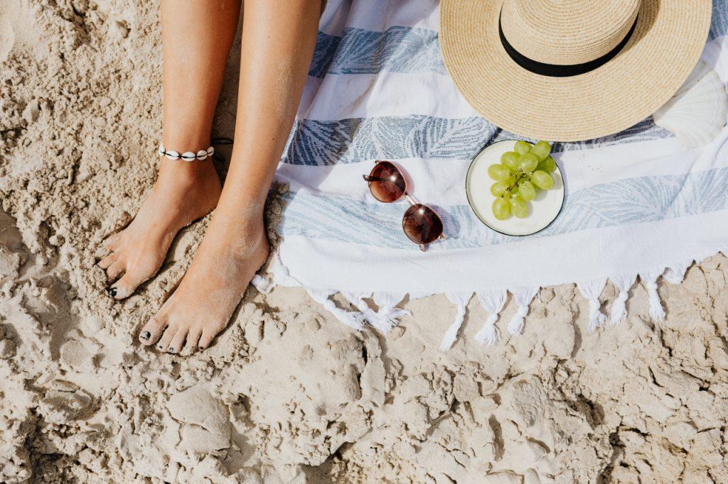Pies de mujer en la arena junto a accesorios de playa