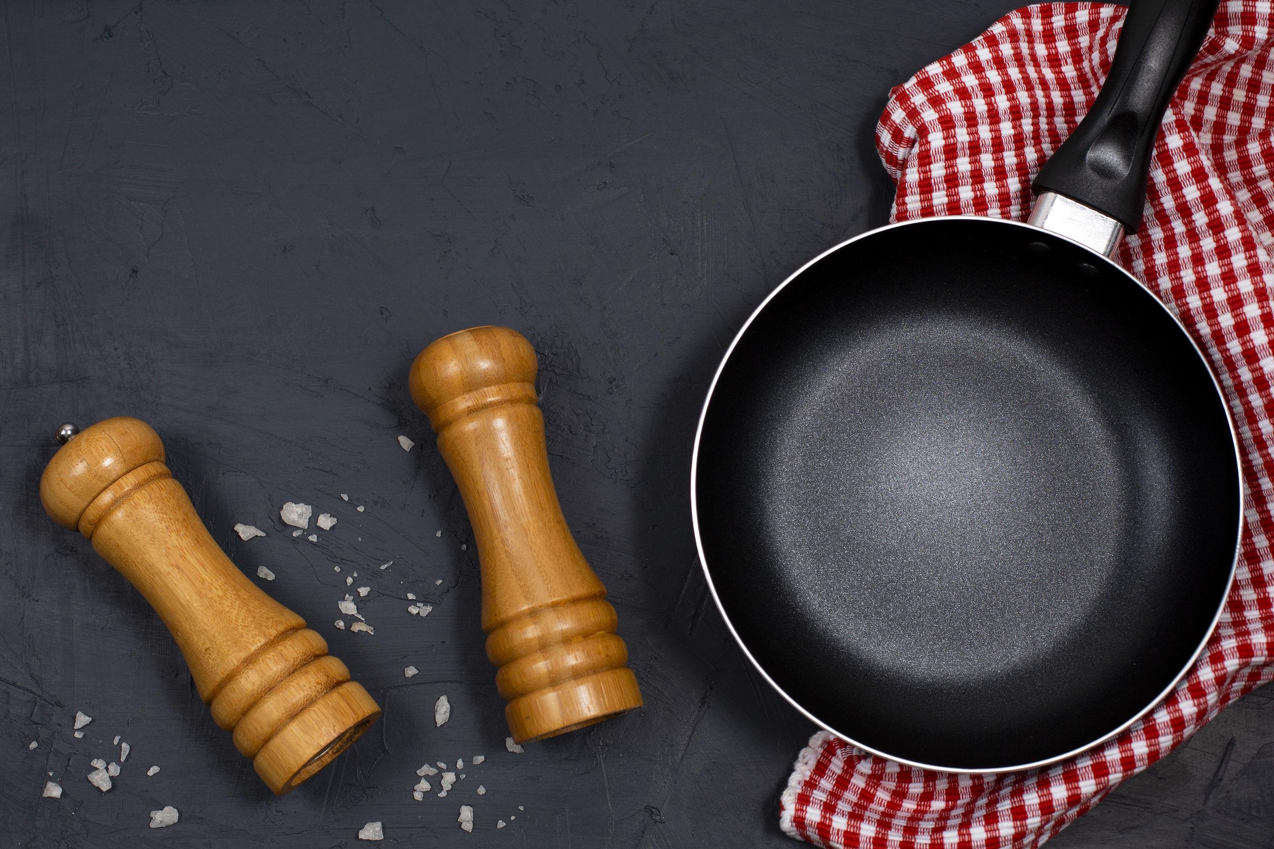 sartén negra con pimienta y sal marina en la mesa negra