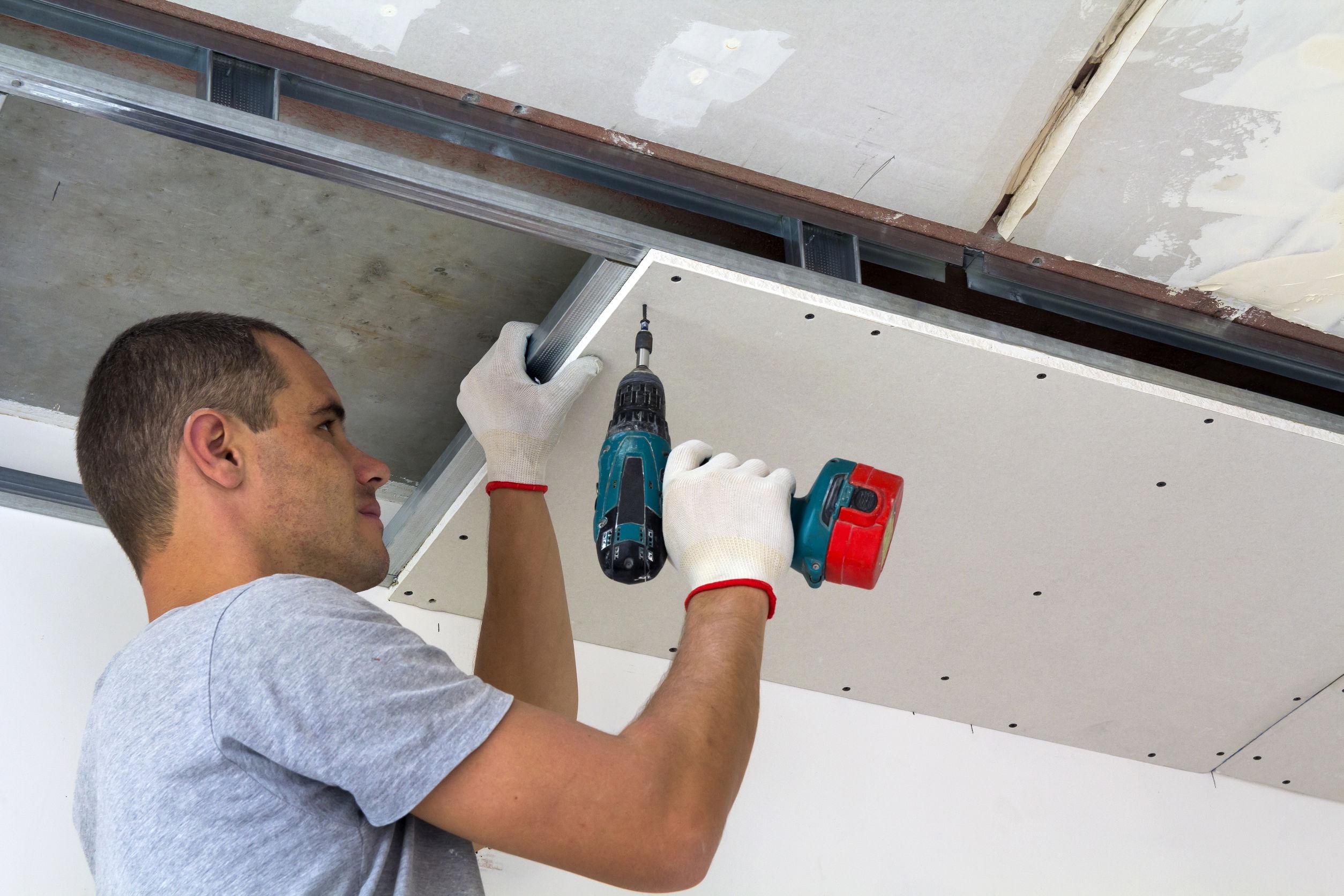 El trabajador de la construcción monta un techo suspendido con paneles de yeso y fija los paneles de yeso al marco de metal del techo con un destornillador