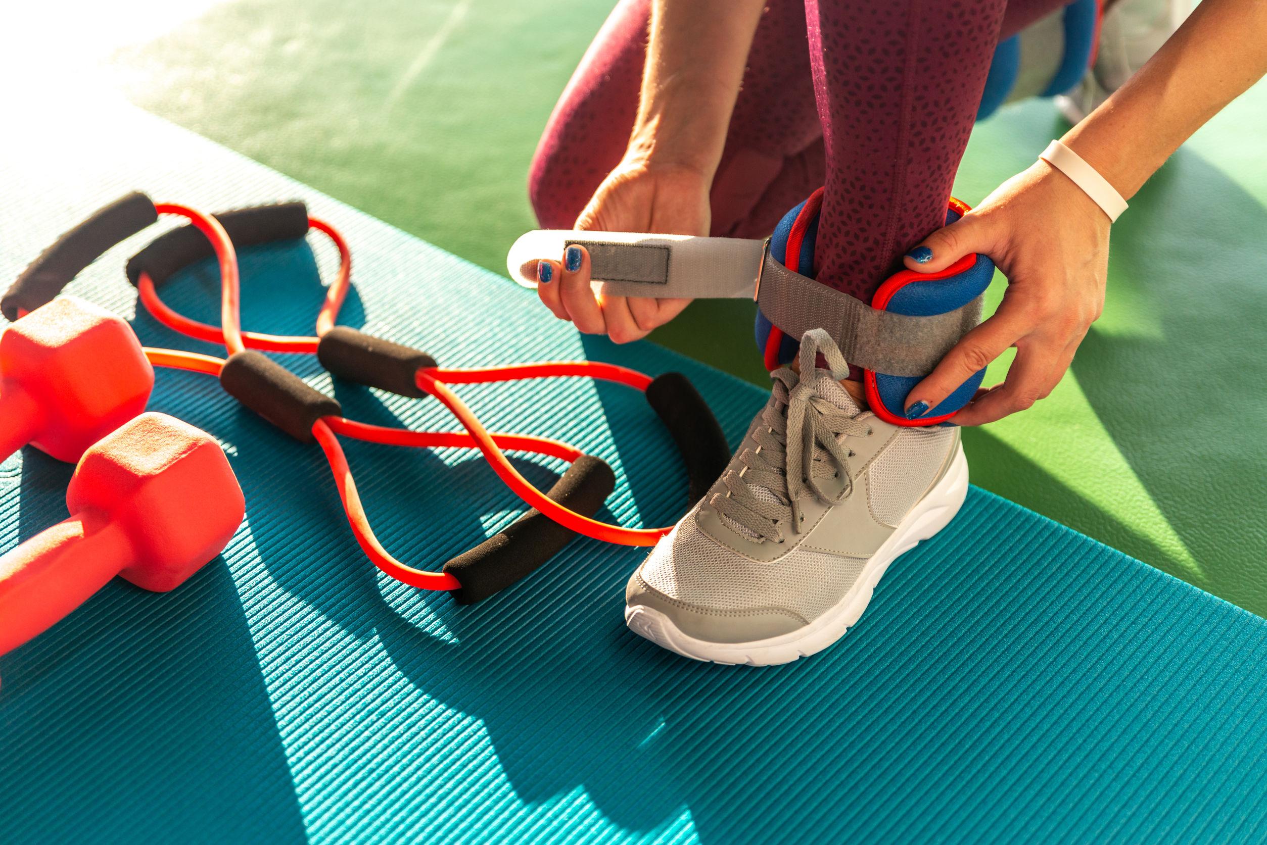 Mujer poniéndose pesas en los tobillos antes de comenzar un entrenamiento