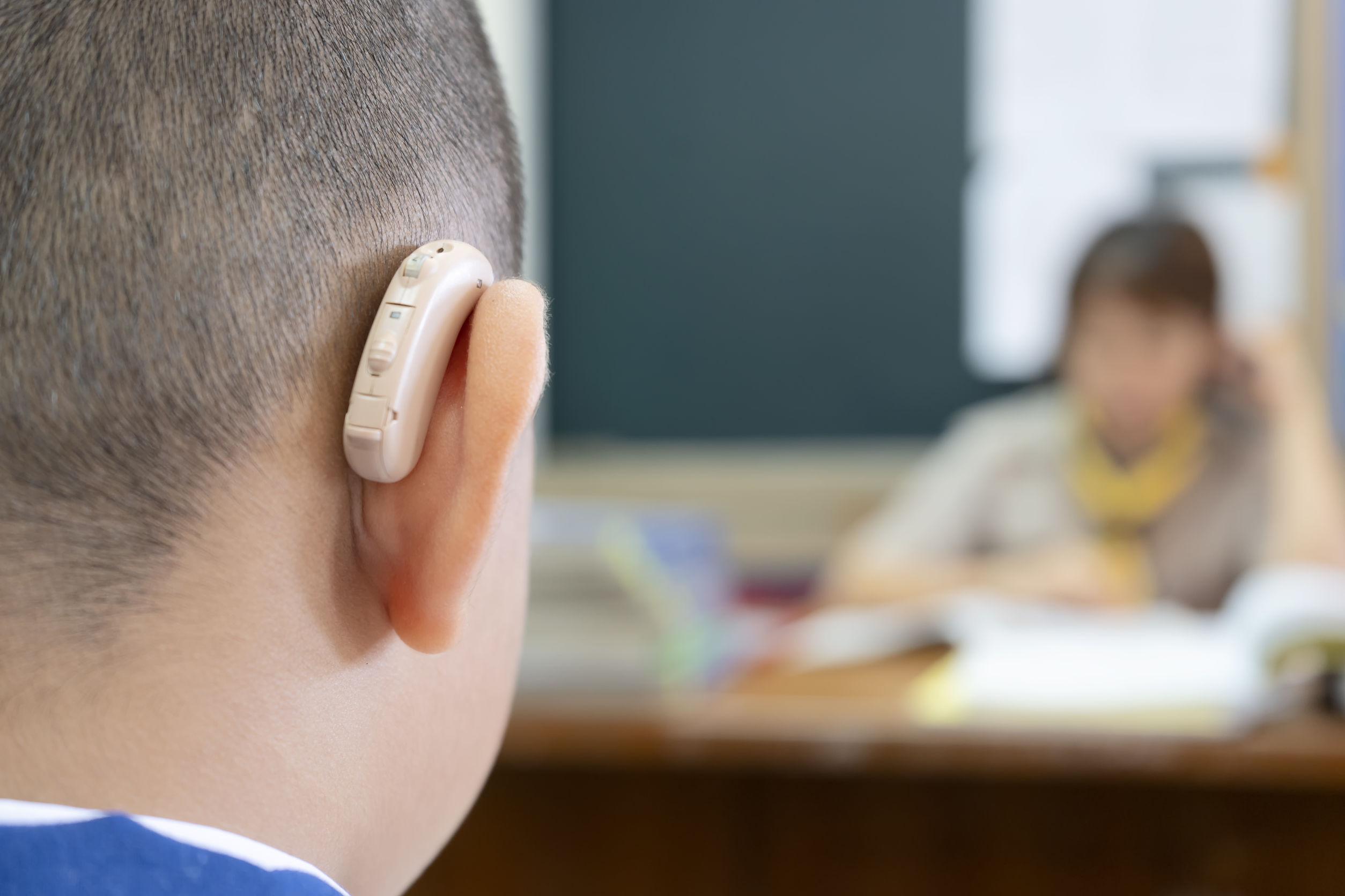 Niño usando audifonos para sordo