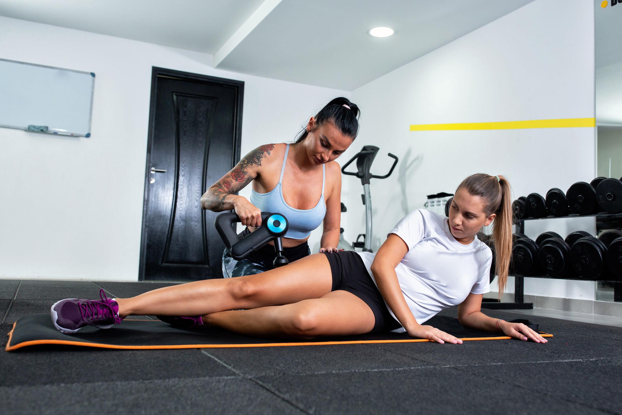 Mujer dando masaje a compañera con pistola de masaje
