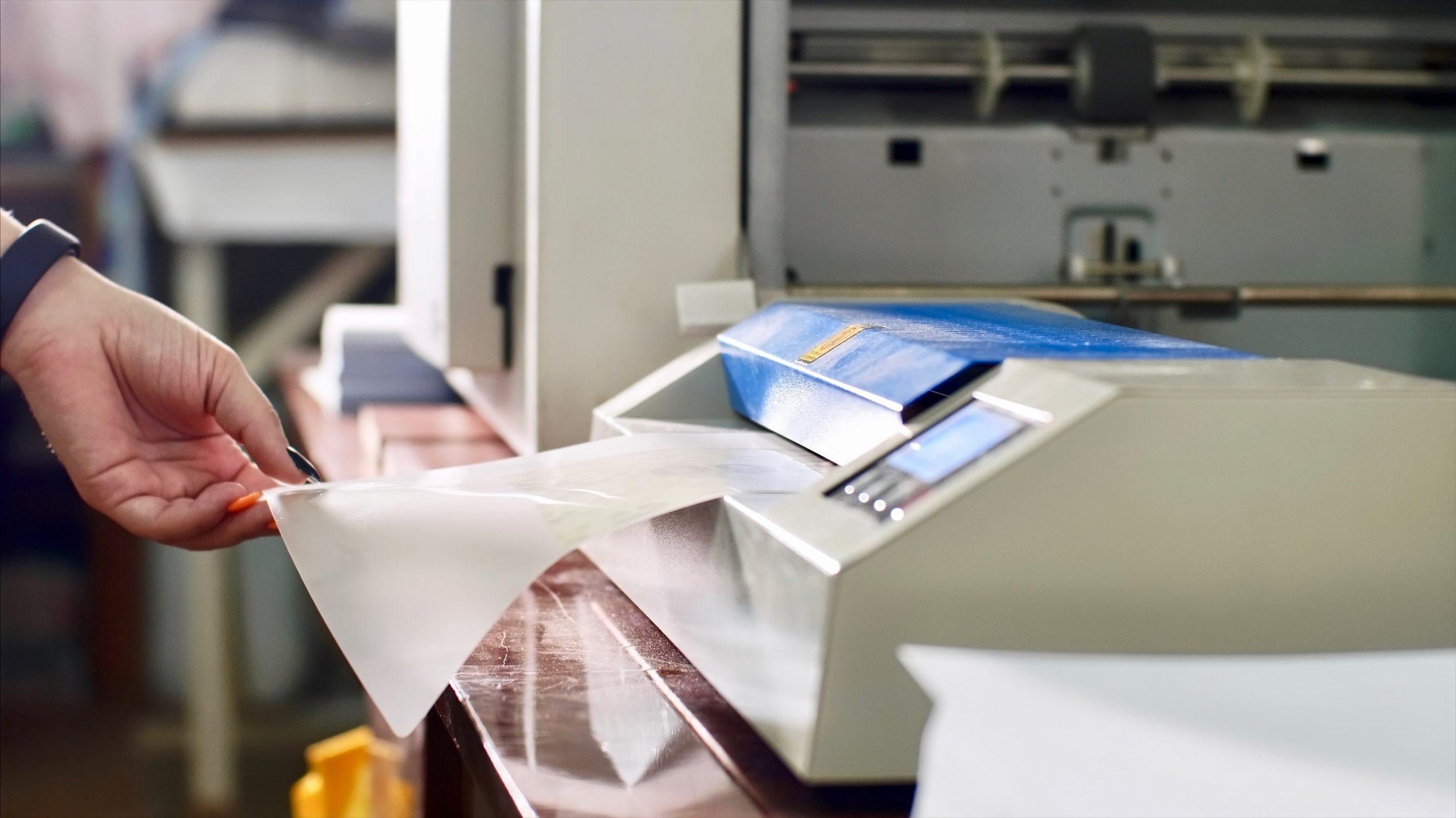 La mujer está laminando papel en la laminadora de la máquina laminadora en tipografía.