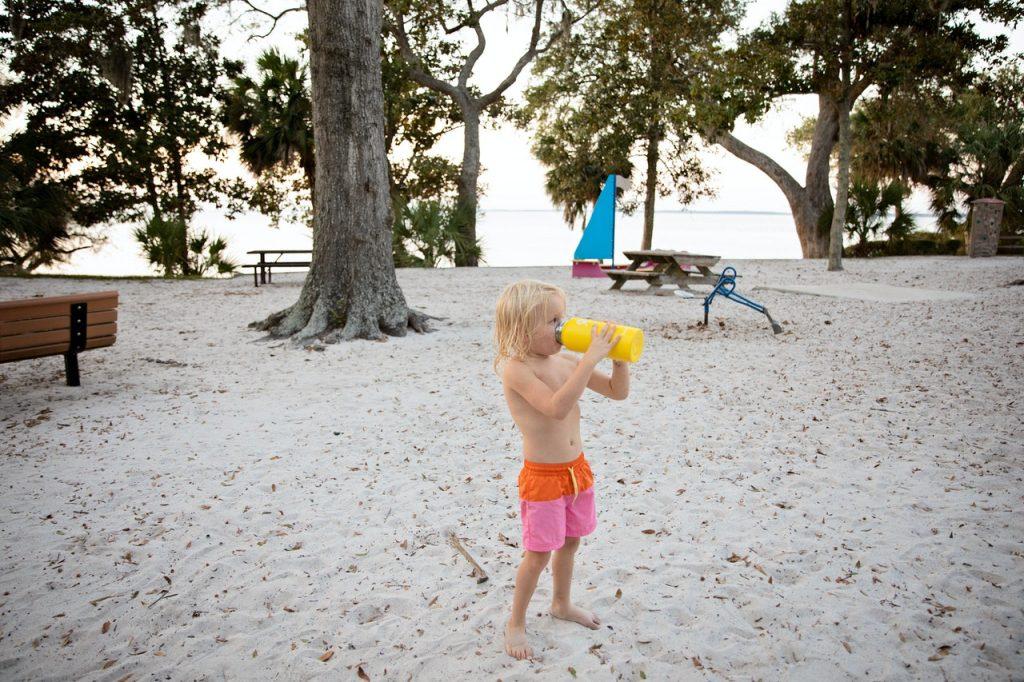 Niño en la playa bebiendo agua de botella