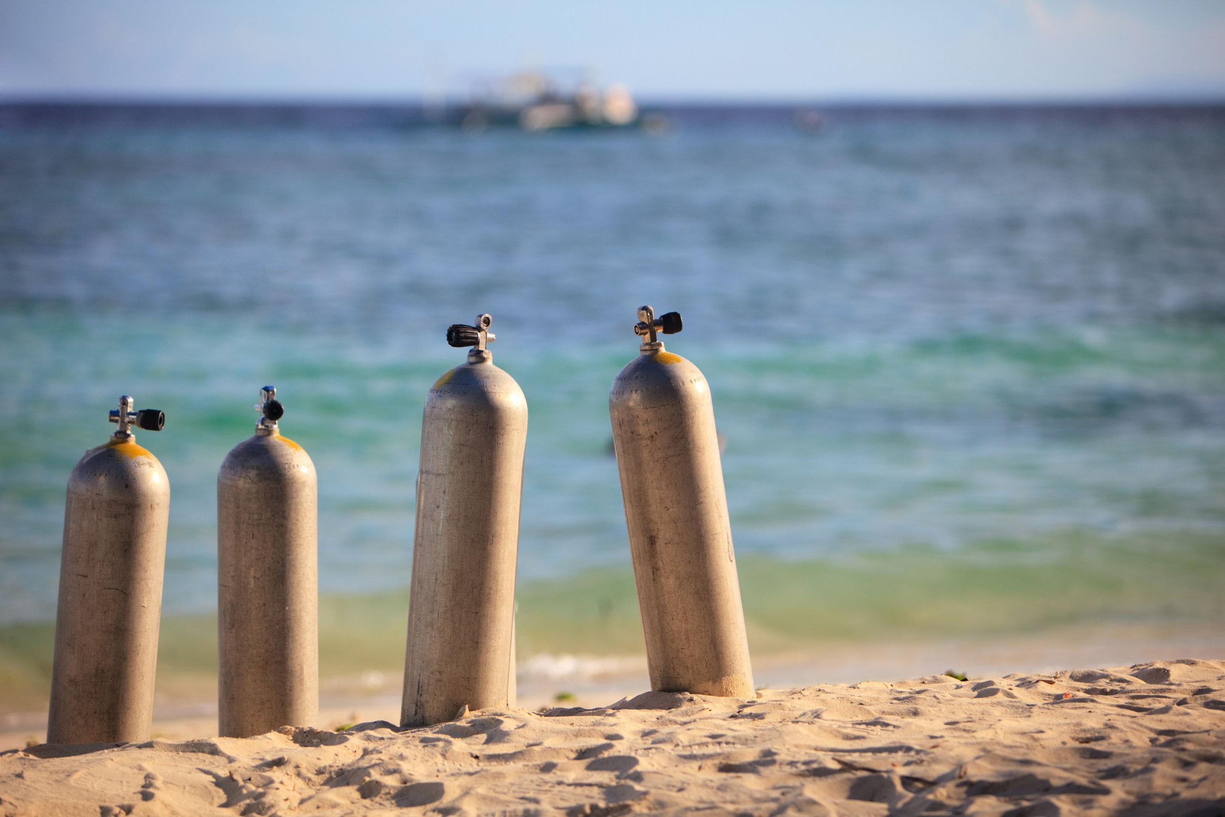Varios tanques de aire comprimido en la arena de la playa
