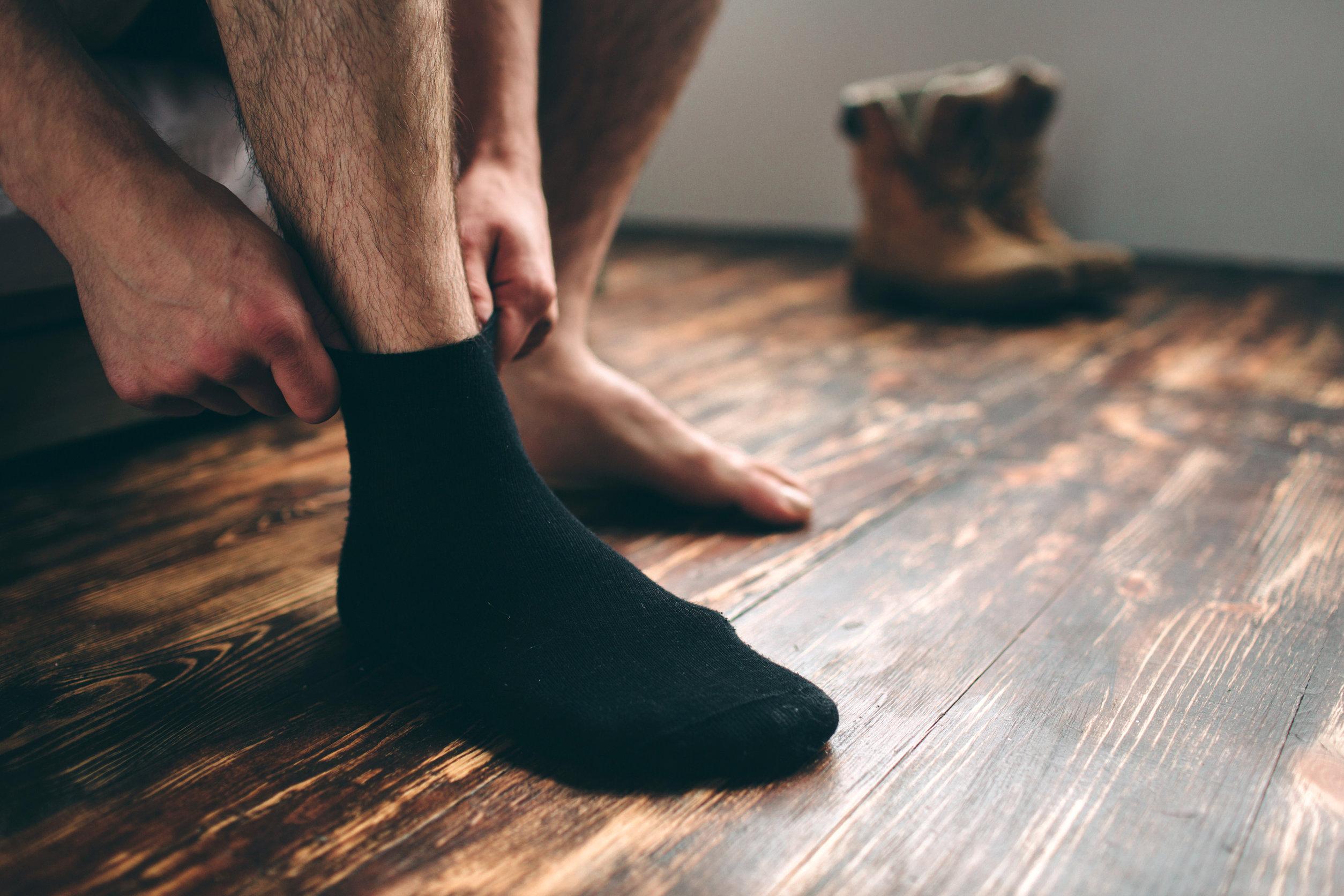 Hombre poniendose calcetines negros